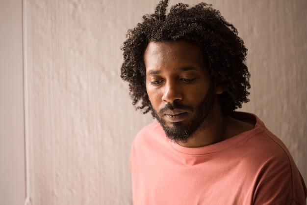 Close up africano novo da cara do homem, chocado e sério, perto de uma janela.
