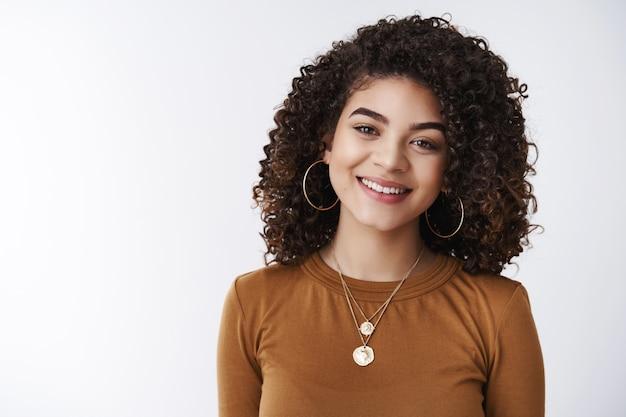 Close-up agradável cabelo escuro encaracolado gerente de atendimento ao cliente feminino sorrindo amplamente pronto para ajudar a expressar interesse felicidade sorrindo dentes brancos encantado com uma conversa positiva, plano de fundo do estúdio
