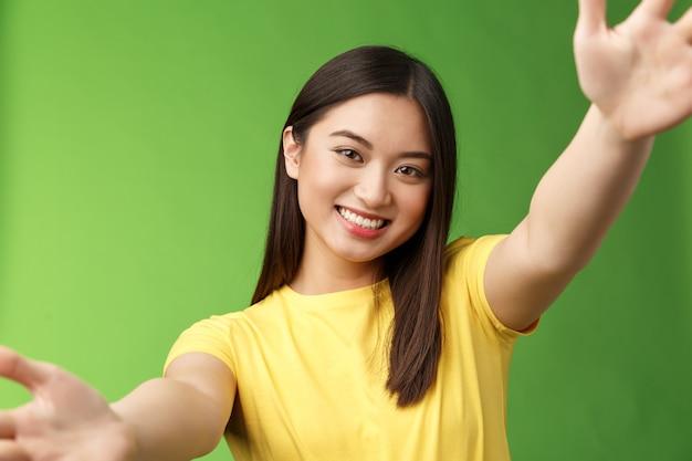 Close-up alegre fofa asiática amigável mulher espalhou as mãos segurando a câmera com os dois braços, sorrindo amplamente, tomando selfie, comunicar estudo familiar tablet digital no exterior, sentir feliz fundo verde.