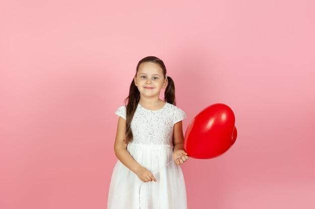 Close-up alegre garota em um vestido branco segurando um balão em forma de coração vermelho