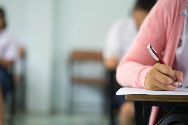 Close-up alunos escrevendo e lendo exercícios de folhas de respostas de exame em sala de aula da escola com o estresse.