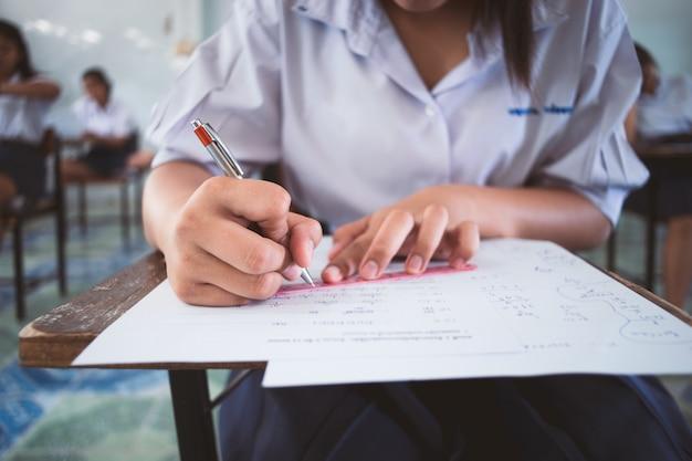 Close-up alunos escrevendo e lendo exercícios de folhas de respostas de exame em sala de aula da escola