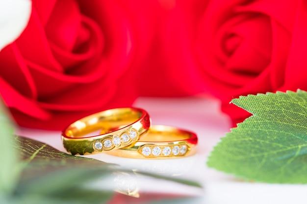 Close-up anel de ouro e rosas vermelhas em branco