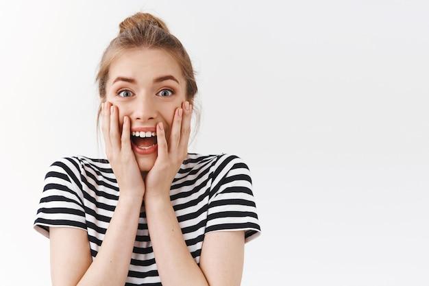 Close-up animada, divertida mulher bonita com coque bagunçado, camiseta listrada, grito de empolgação e espanto reagem a notícias maravilhosas e incríveis, com um fundo branco surpreso