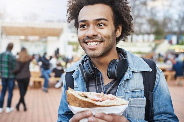 Close-up ao ar livre de um jovem alegre e emotivo de pele escura com penteado afro, usando fones de ouvido no pescoço e casaco jeans, segurando um sanduíche e olhando para o lado enquanto está no festival da cidade