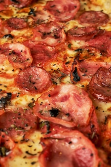 Close up apetitoso da pizza de pepperoni do fundo que enche o quadro.