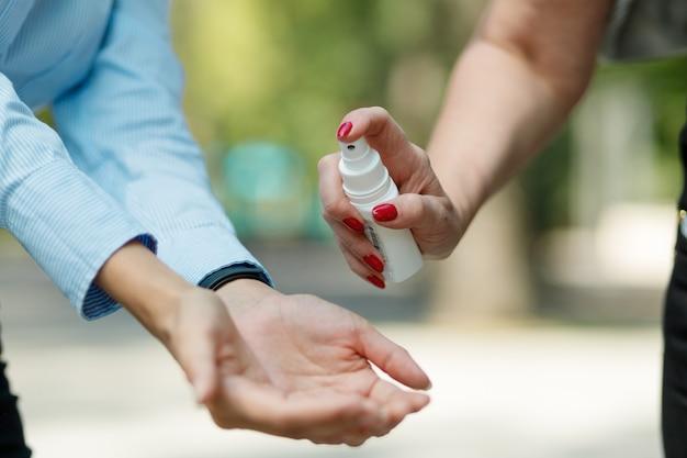 Close-up aplicando desinfetante para as mãos para limpar e desinfetar as mãos ao ar livre.