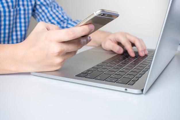 Close-up as mãos dos homens de negócios que vestem uma camisa de manta usando telefones celulares e laptop na sala.