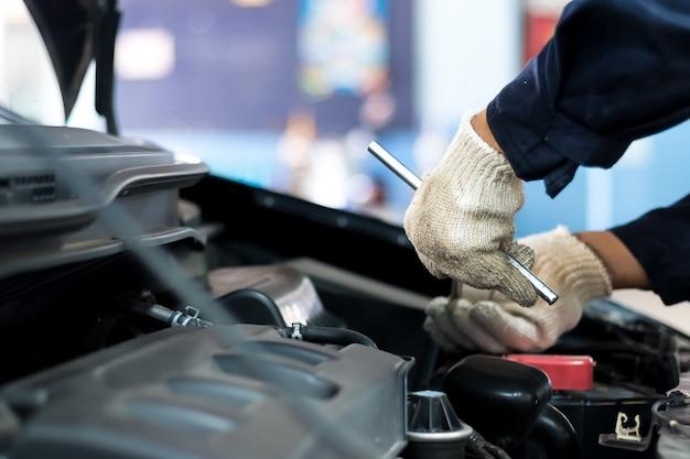 Close up, as pessoas são reparar um carro use uma chave inglesa e uma chave de fenda para o trabalho.