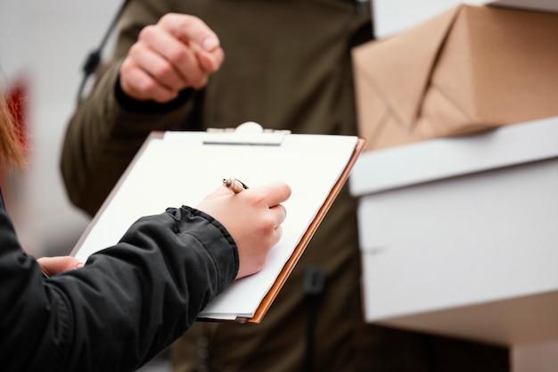 Close up assinando para entrega de pacote