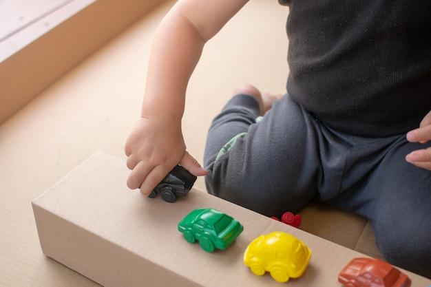 Close-up, baby sentar e brincar com o carro de brinquedo