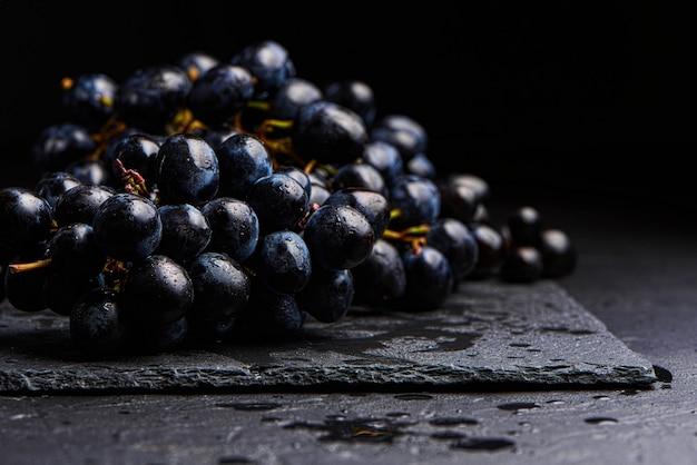 Close-up, bagas de cacho escuro de uva com pouca luz isoladas no fundo preto, gotas de água