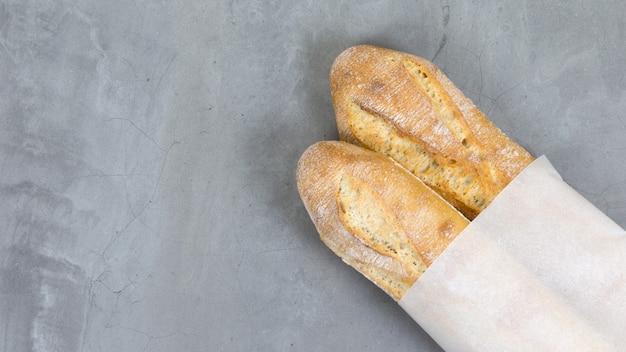Close-up baguetes irritadas, pão cozido no fundo da mesa de pedra cinza pão francês embalagem de papel ecologicamente correta com espaço de cópia