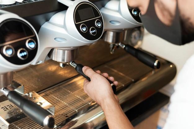 Close up barista com máscara fazendo café