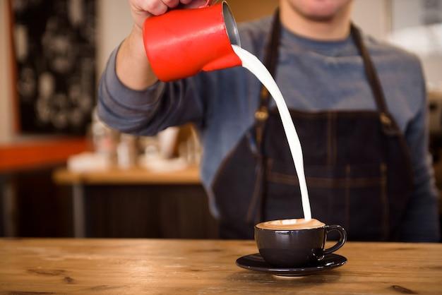 Close-up barista derramando muito leite na xícara de café, fazendo latte art.