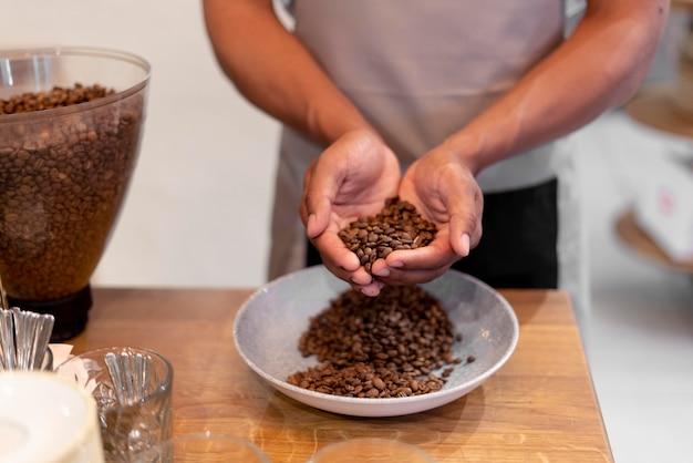 Close-up barista segurando grãos de café