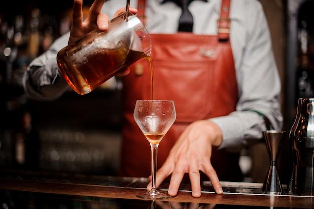 Close-up barman derramando cocktail de álcool vermelho brilhante em vidro chique