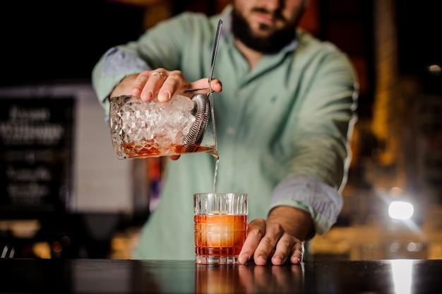 Close-up barman derramando cocktail em vidro chique