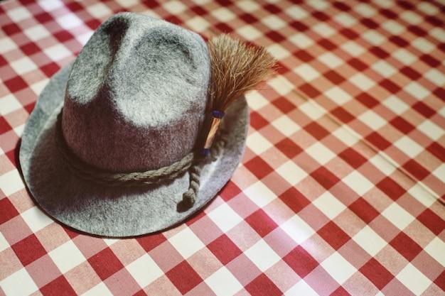 Close-up bávaro tradicional do chapéu em um fundo checkered vermelho e branco. oktoberfest