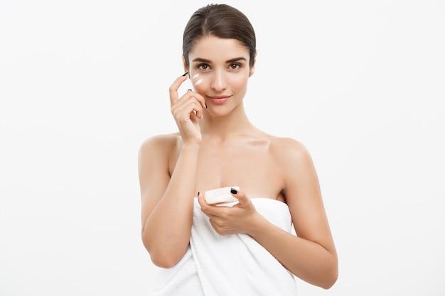 Close-up beautiful caucasian woman face portrait aplicando um pouco de creme no rosto para a pele