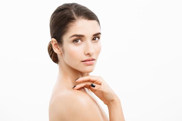 Close-up beautiful young woman tocando sua pele no fundo branco.