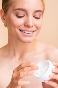 Close-up bela modelo usando creme para o rosto