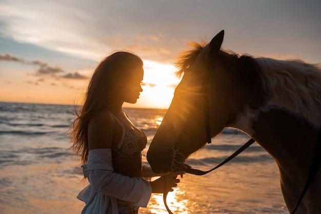 Close-up: beleza morena jovem se divertindo com o cavalo na praia. pôr do sol