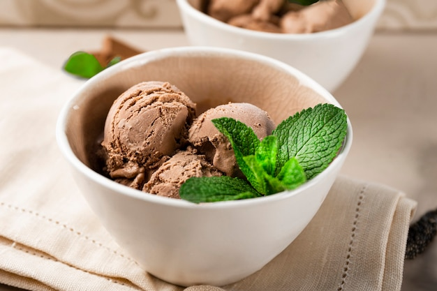 Close-up bolas de sorvete de chocolate caseiro com hortelã em uma tigela.