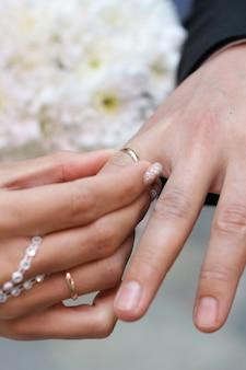 Close up bonito da mão da aliança de casamento dourada.