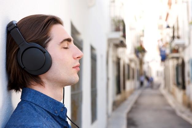 Close-up bonito homem meditativo com fones de ouvido na rua da cidade