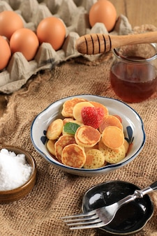 Close up bowl full of tiny pancake ou popular como cereal pancake, lanche viral popular durante quarentena em 2020. servido acima fundo juta marrom com garfo, imagem versão vertical