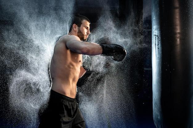 Close-up boxer masculino no saco de pancadas, câmera lenta.