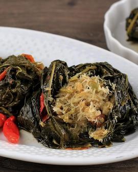 Close up buntil é um alimento tradicional indonésio feito de folhas de mamão / mandioca recheadas com coco ralado, petai cina e peixe anchova. popular na culinária javanesa e sudanesa