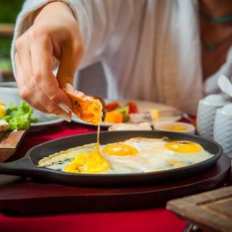 Close-up café da manhã em uma mesa com uma toalha de mesa vermelha ovos fritos, queijo queijo, pepino, tomate, alface, café