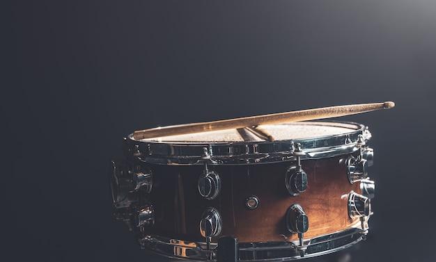 Close-up, caixa, instrumento de percussão contra um fundo escuro com iluminação de palco.