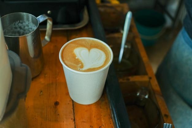 Close up cappuccino com arte latte na mesa de madeira