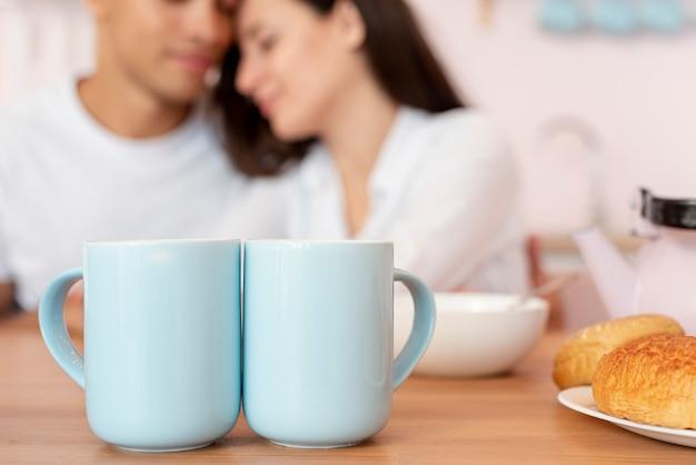 Close-up casal borrado com canecas azuis
