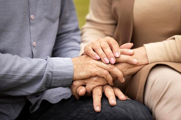 Close-up casal de mãos dadas