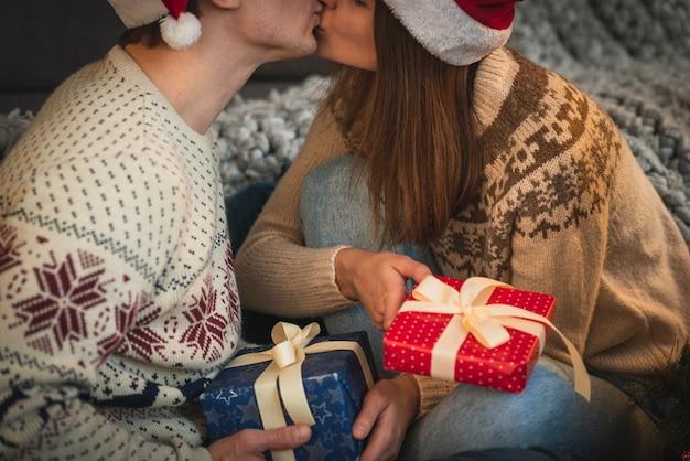 Close-up casal fofo com presentes de natal beijando