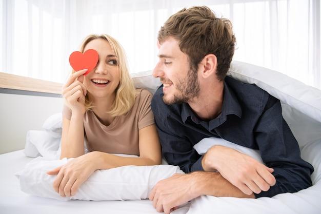 Close-up casal jovem caucasiano romântico vivendo juntos no quarto na manhã. homem e mulher mostrando um cartão de coração vermelho. retrato de casal, namorado e namorada afetuoso no dia dos namorados.