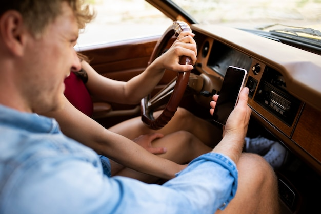 Close-up casal no carro com smartphone