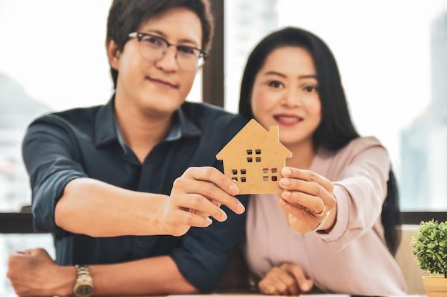 Close-up casal segurando modelo em casa, escolha de compra em casa