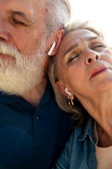 Close-up casal sênior com fones de ouvido