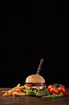 Close-up caseiro de hambúrguer com carne, tomate, alface, queijo, cebola e batatas fritas na mesa de madeira.