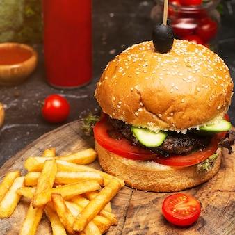 Close-up caseiro do hamburger com carne, tomate, alface, queijo e batatas fritas na placa de corte. comida rápida