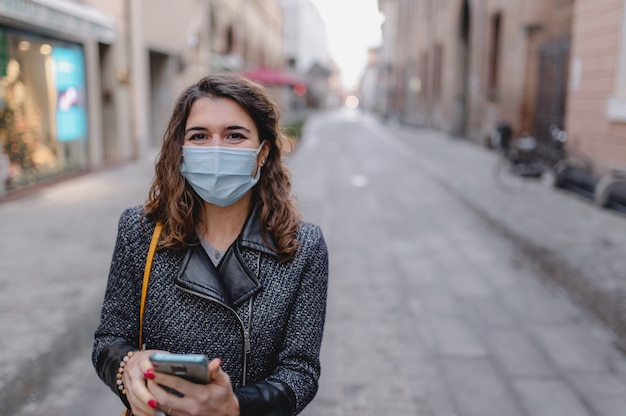 Close-up caucasiana sorridente jovem andando no centro de uma cidade usando smartphone durante o inverno frio.