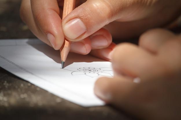 Close-up childs mão desenha uma flor com um lápis em uma folha branca de papel, foco seletivo