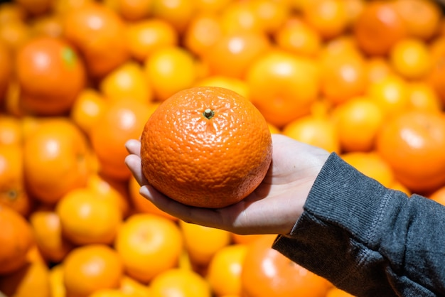 Close-up cliente feminino mão pegar uma laranja fresca no mercado