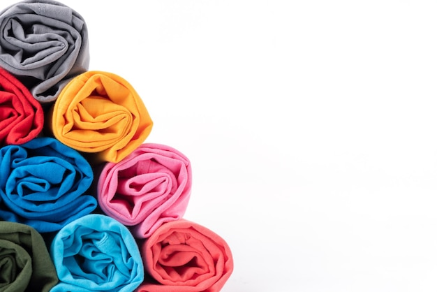 Close-up colorido de rolos de algodão t-shirt feita em forma de pirâmide isolada no fundo branco.