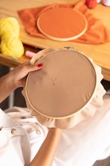 Close-up com as mãos costurando em casa